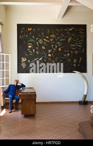 A worker looks bored in the empty natural history museum in Maputo, Mozambique sitting under an illustration of - Stock Photo