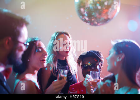 Dressy multiethnic group of friends gathered together and celebrating momentous event in nightclub, they laughing - Stock Photo