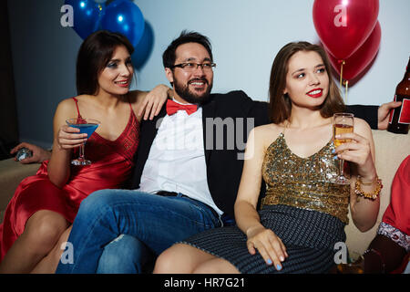Male and female clubbers celebrating momentous event with alcohol: they sitting on couch and looking away joyfully - Stock Photo