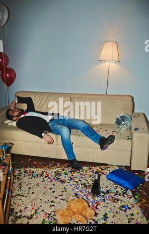 Messy room after wild party: colorful confetti thrown everywhere, empty alcohol bottles and champagne flutes standing - Stock Photo