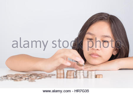 Little Asian girl saving money putting coins On a white table - Stock Photo