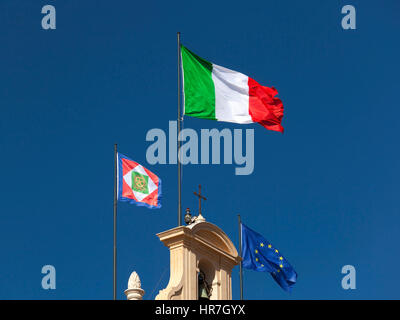 Italian flag displayed on the bell tower of the Quirinal, together with the Presidential pennant and the flag of - Stock Photo