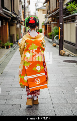 Maiko dressed with traditional attires posing to the camera in a small alley on her way to work. - Stock Photo