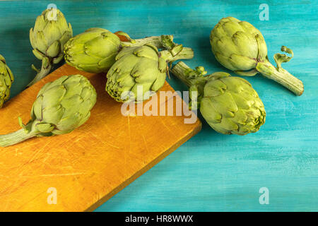A photo of artichokes on a vibrant turquoise texture with a place for text - Stock Photo