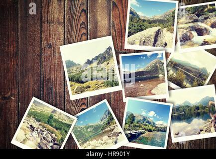 Heap of the vintage photos from holiday in mountains with traditional white frame placed on wooden desk. - Stock Photo