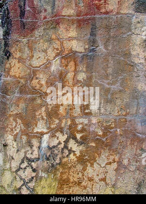 Closeup of a cracked, rusty and multicolored concrete wall. Grunge abstract texture of an old surface. Prominent - Stock Photo
