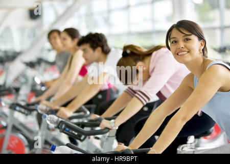 People in a spinning class at the gym - Stock Photo