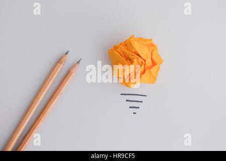 In Search of New Idea or Innovation. Yellow crumpled paper ball as a light bulb and two pencils. - Stock Photo