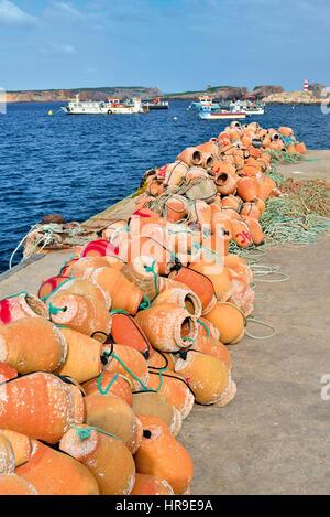 Portugal: Terracotta vases 'alcatruzes' lying on the quay of harbor Porto da Baleeira in Sagres - Stock Photo