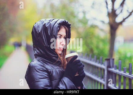 Girl in autumn or spring in a black jacket. He drinks coffee or tea in hand outdoors. Resting in the city. Life - Stock Photo