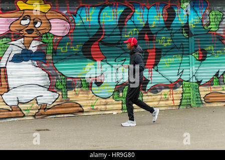 A young  black male wearing headphones walking past brightly coloured graffiti on the front of a disused shop on - Stock Photo