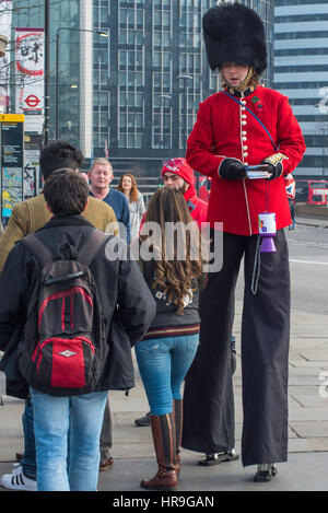 A man wearing stilts dressed as a Coldstream Guard soldier handing out leaflets and collecting for charity in London. - Stock Photo