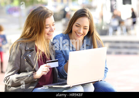 Two friends buying on line with credit card and a laptop sitting in a bench in the street with an urban background - Stock Photo
