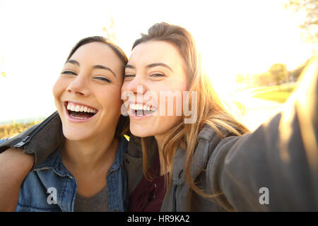 Two funny friends taking selfies outdoors in the street at sunset with a warm light in the background - Stock Photo