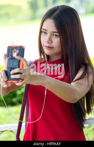 Young girl in red dress taking a selfie with smartphone - Stock Photo