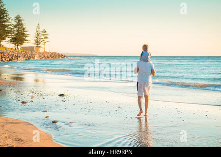 Father giving son piggyback ride on beach - Stock Photo
