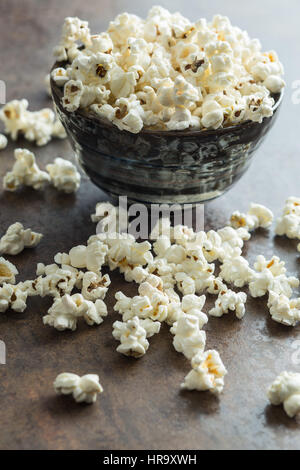 Popcorn in ceramic bowl on rusty background. - Stock Photo