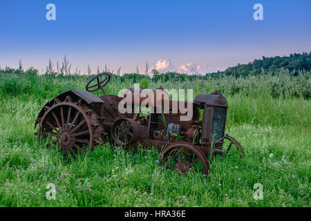 An old rusty McCormick-Deering tractor sits in an overgrown field. - Stock Photo