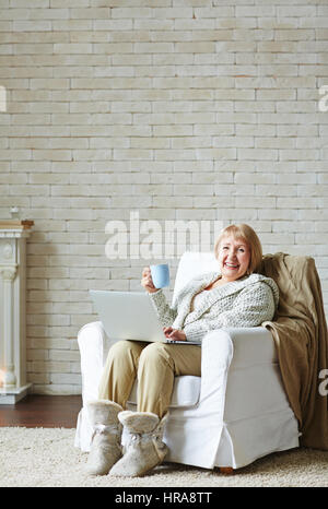 Joyful senior woman looking at camera with wide smile while checking her e-mail with tea mug against white brick - Stock Photo