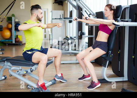 Working out in gym: Side view of beutiful yong woman doing arm excercise on cable machine with personal fitness - Stock Photo