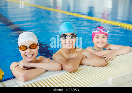 Three healthy smiling children looking to camera wearing swimming goggles and caps in water at tiled border of blue - Stock Photo