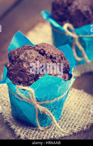 Homemade chockolate muffins in paper cupcake holder over wooden backround - Stock Photo