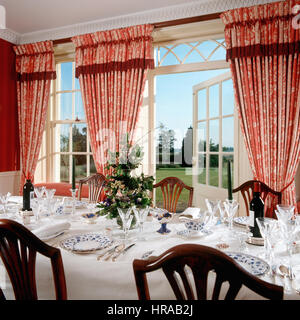 China and glassware in dining room with red patterned curtains framing spectacular views to garden - Stock Photo
