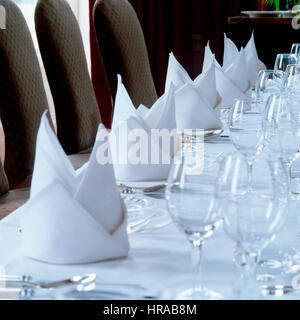 A set table with folded napkins. - Stock Photo