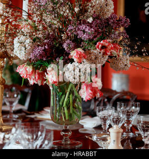 A vase of flowers on a dining table. - Stock Photo