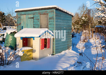 A green painted shed stands on an allotment coverd in snow with a childs play house mirroring it aslo covered in - Stock Photo