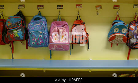 Childrens rucksacks hung on their pegs in a daycare - Stock Photo