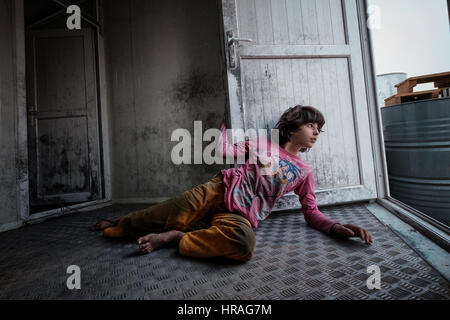 A mentally handicapped refugee girl age 9, chained to a toilet by the ankle in Zakho IDP camp near Dohuk, Kurdistan, - Stock Photo