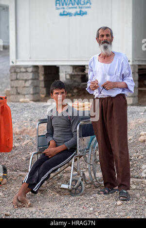 disabled refugee boy and his father in Zakho IDP camp near Dohuk, Kurdistan, Iraq. - Stock Photo