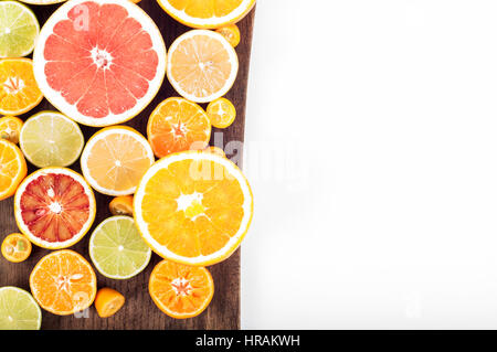 Colorful fresh citrus fruit on wooden background. Orange, tangerine, lime, blood orange, grapefruit. Fruit background. - Stock Photo