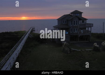 dramatic sunset over summer vacation rental house and fishing pier Pamlico Sound, Outer Banks, North Carolina - Stock Photo