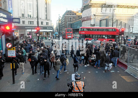 Red double decker buses, traffic & pedestrians crossing streets on busy Oxford Street by Tottenham Court tube station - Stock Photo