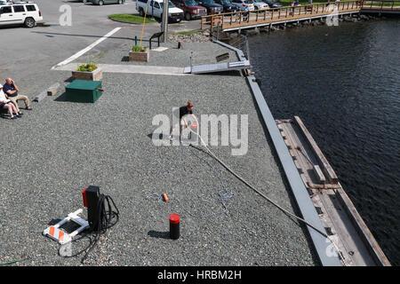Line handler aids docking of  the Century-old Motor Vessel Katahdin at Moosehead Marine Museum - Stock Photo