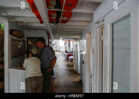 Day trip passengers on a weather deck aboard the Century-old Motor Vessel Katahdin - Stock Photo