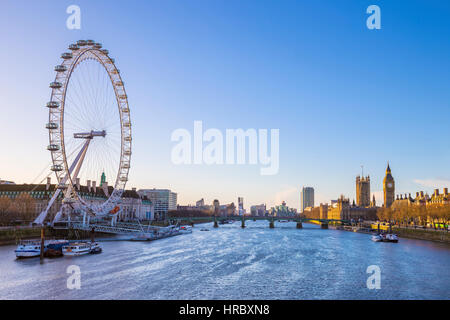 London's skyline view at sunrise with famous landmarks, Big Ben, Houses of Parliament and ships on River Thames - Stock Photo