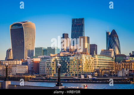 London, UK - The world famous business district of London with skyscrapers and clear blue sky at sunrise - Stock Photo