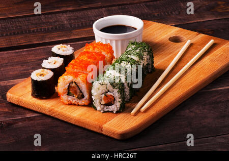 Sushi rolls and soy sauce with chopsticks served on wooden slate in a restaurant - Stock Photo