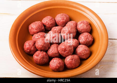 Raw meatballs in plate on a white wooden table background - Stock Photo
