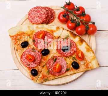 Two pieces of fresh homemade salami pizza with olives, salami and tomatoes on a wooden board - Stock Photo
