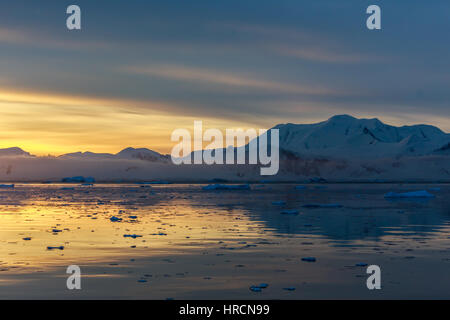 Sunset over idyllic lagoon with mountains and icebergs in the background at the Lemaire Strait, Antarctica - Stock Photo
