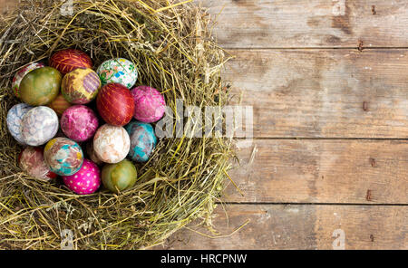 Colorful painted and decorated Easter eggs in a nest of hay - Stock Photo