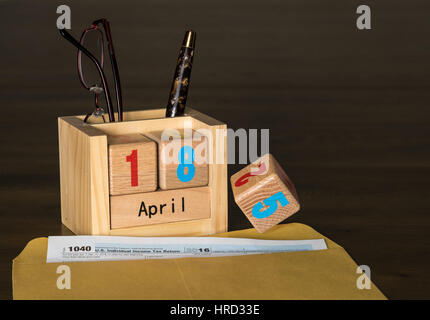 Wooden letters in calendar with Form 1040 income tax for 2016 showing tax day for filing is April 18 2017 instead - Stock Photo