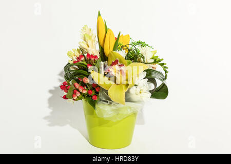 colorful floral bouquet of orchids, tulips, chrysanthemums,  and red hypericums  in vase isolated on white background - Stock Photo