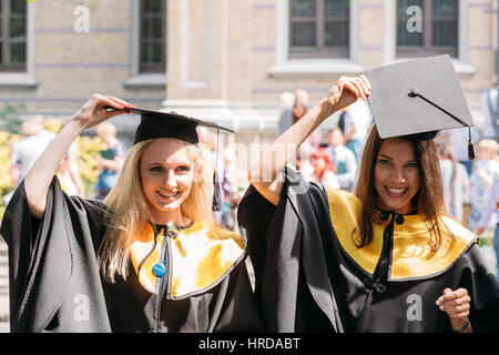 Riga, Latvia - July 1, 2016: Two young women graduates of the University of Latvia dressed in gown graduates and - Stock Photo