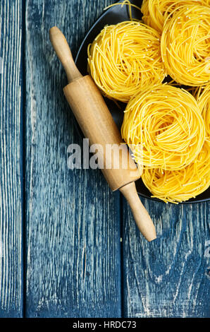 raw noodles from chicken yolks on a table - Stock Photo