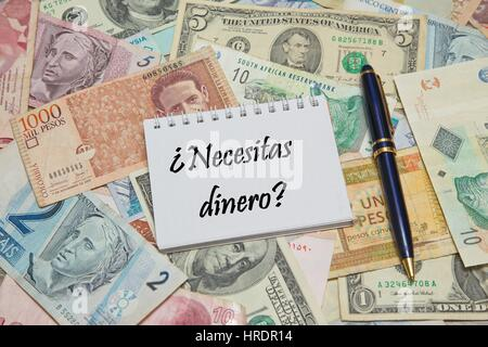 Notebook page with SPANISH text 'NECESITAS DINERO' (NEED MONEY), background from different world Currencies - Stock Photo